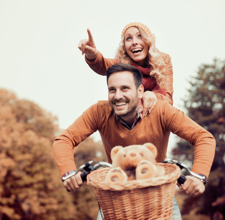 公園での楽しみを持っている若いカップル。自転車のために行く幸せな若いカップルは公園で秋の日に乗る。