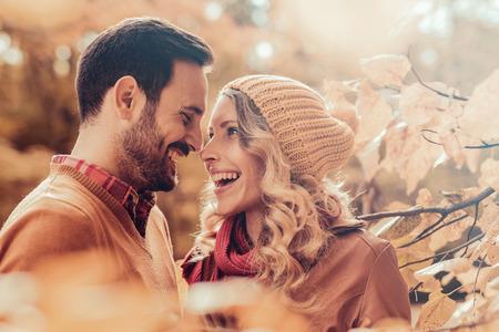 屋外の愛の若いカップル。夫婦笑みを浮かべて、秋の季節を楽しんでします。