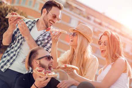 特寫四個年輕人開朗的人吃的朋友考慮他們的比薩餅切片pizza.Group。 版權商用圖片