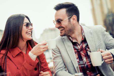 幸せなカップルは、コーヒー ショップでコーヒーを楽しんでいます。