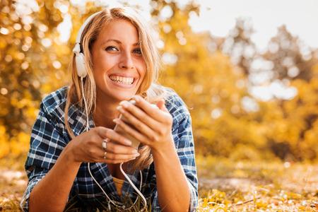 Mujer joven que escucha la música en un teléfono inteligente al aire libre. Foto de archivo