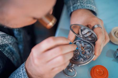 Close-up portret van een horlogemaker bij work.A horlogemaker of reparatie man in actie, het bekijken van zeer nabij een Zwitsers horloge. Stockfoto - 71253852