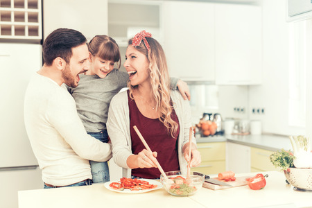 Happy family preparing meal from fresh vegetables.