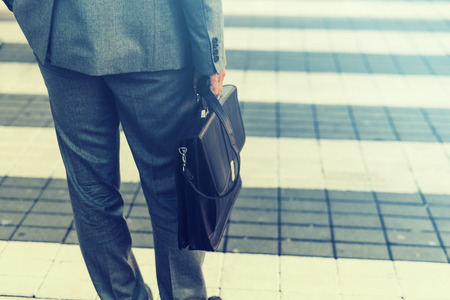 Cropped view of businessman holding a briefcase outdoors. Stock Photo