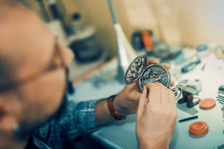 Cerca de retrato de un relojero en work.A relojero o reparación hombre en acción, ver muy de cerca un reloj. Foto de archivo