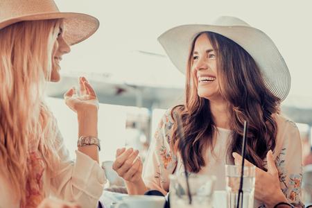 Glimlachend jonge vrouwen met kopjes koffie in cafe.