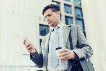 Close-up portret van een succesvolle zakenman met behulp van een slimme telefoon, terwijl die zich door een modern kantoorgebouw.