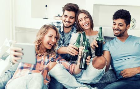Vrolijke groep vrienden plezier thuis, nemen selfie.