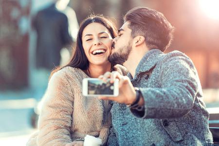 Un couple heureux d'avoir du plaisir et de prendre un selfie.They profitent de la vie urbaine.