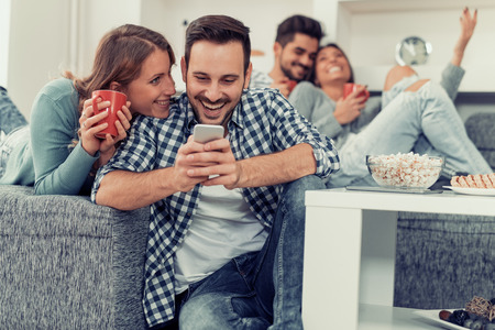 groupe Enthousiaste d'amis ayant du plaisir à la maison, en utilisant un téléphone intelligent.