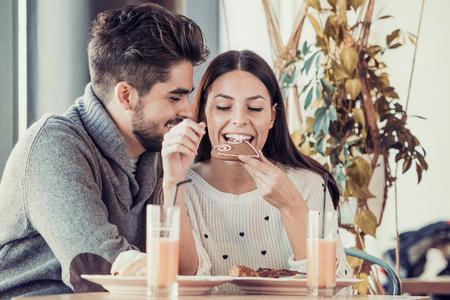Happy young couple having breakfast in cafe,enjoying together. 版權商用圖片