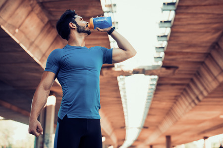 Man drinking water from bottle after fitness sport exercise.  版權商用圖片