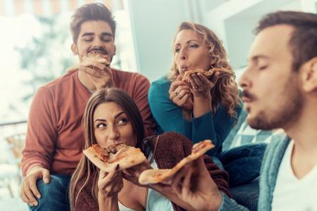 Vrolijke groep vrienden plezier thuis, het eten van pizza.