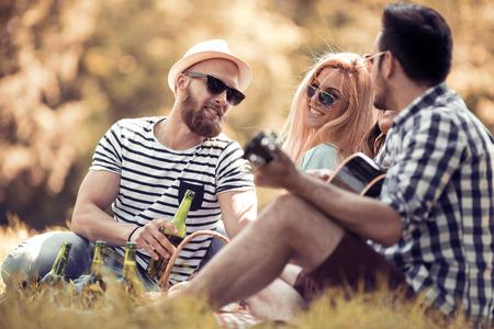 Gelukkig jonge vrienden met picknick in het park.They zijn allemaal blij, plezier, glimlachend en gitaar spelen.