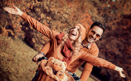 Happy young couple going for a bike ride on a autumn day in the park. Stockfoto