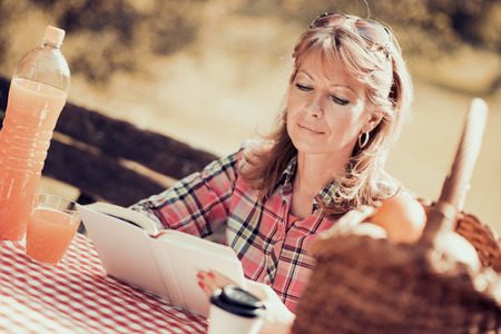 Woman sitting in a park and reading a book. Stockfoto