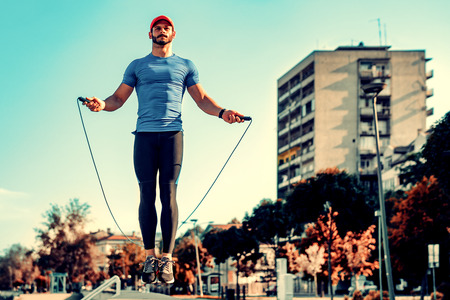 Handsome young sports man skipping rope in the city.