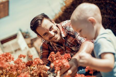 Vader en zoon samen te werken in de garden.Little jongen te helpen zijn vader om bloemen te planten.