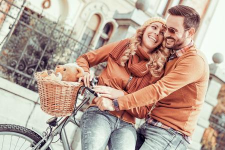 Jong stel met plezier in de city.Happy jonge paar gaat voor een fietstocht op een herfst dag in de stad. Stockfoto