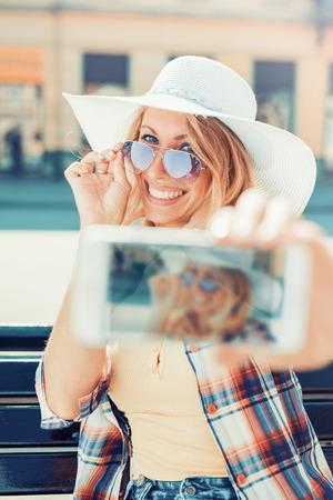 Schoonheid van de jonge vrouw maakt selfie met slimme telefoon, buitenshuis