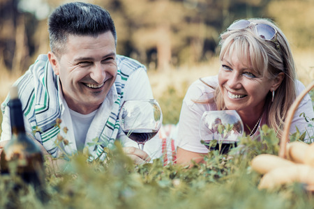 Happy couple in love at a picnic.Couple enjoying red wine on picnic in park. Stockfoto
