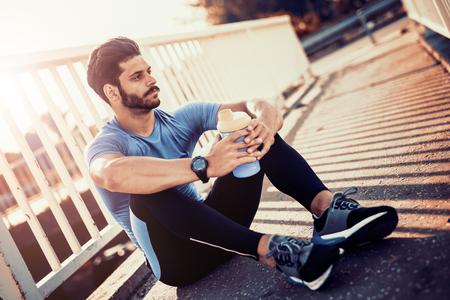Portret van een jonge man drink wat water uit een fles terwijl het zitten en rust na de training.