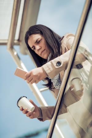 Vrouw gebruikt haar slimme telefoon op de straat, met koffie pauze.