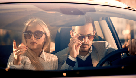 Jong paar samen in de auto - een man rijden, genieten van elkaar. Stockfoto