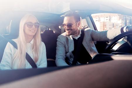Een jonge vrouw en een jonge man lachen in de auto, genieten in de weg trip.The man rijdt.