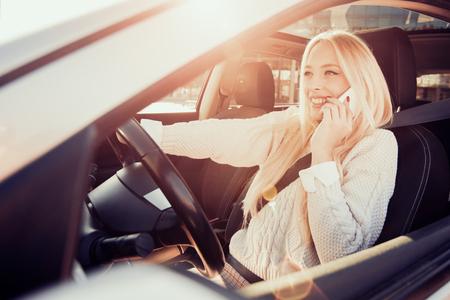 Bestuurder van de vrouw met behulp van een slimme telefoon in de auto.