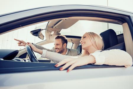 Blij om te reizen together.Joyful jonge paar lachende tijdens het rijden in hun auto.