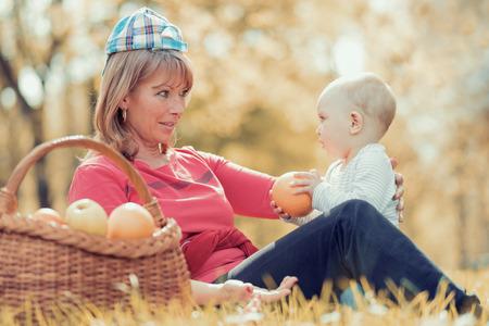 Prachtige middelbare leeftijd moeder en haar schattige kleine zoon met een picknick in het zonnige park.