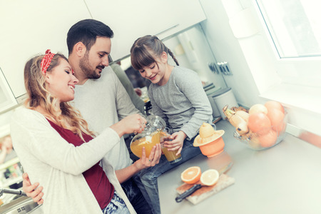 Jonge moeder pour sinaasappelsap aan haar dochter in de keuken. Stockfoto