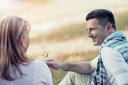 Tir d'un beau couple d'âge mûr sur un pique-nique et de faire un toast.