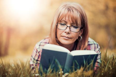 Gelukkige vrouw leest een boek tijdens de lente in het park.