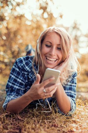 Jonge vrouw luisteren naar muziek op een slimme telefoon buitenshuis. Stockfoto