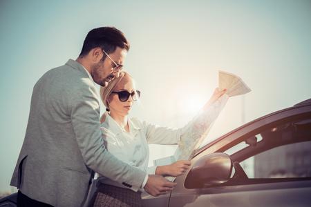Glimlachende man en vrouw met behulp van map op roadtrip.Leisure, road trip, reizen en mensen concept.