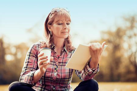 Vrouw zitten in een park en het lezen van een boek.