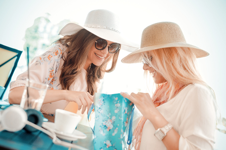 Two young women sharing their new purchases with each other.They having coffee break after good shopping.