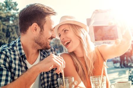 Gelukkig jong paar dat selfie met slimme telefoon op cafe, having fun.