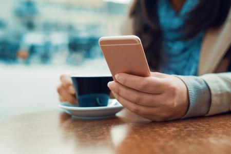 Femme au café avec un téléphone intelligent ayant une pause-café.
