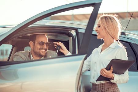Auto dealership.Young man ontvangen auto sleutel van verkoopster.