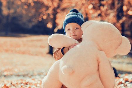Schattige kleine jongen met zijn teddy beer vriend in het park.