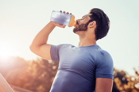 Man drinkwater uit de fles na fitness sport oefening.