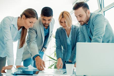 Business team in een office.Cheerful groep van mensen uit het bedrijfsleven te kijken naar een digitale tablet.Discussing project. Stockfoto