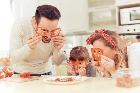 préparer Bonne jeune famille le déjeuner dans la cuisine et profiter ensemble.