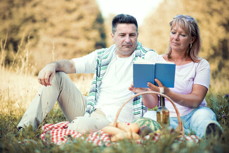 Happy mature couple lying on grass and reading a book in the countryside.