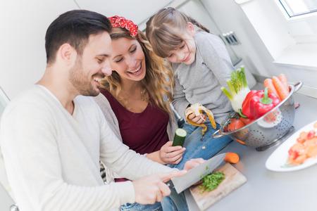 Gelukkig jong gezin voorbereiding van de lunch in de keuken en samen genieten.