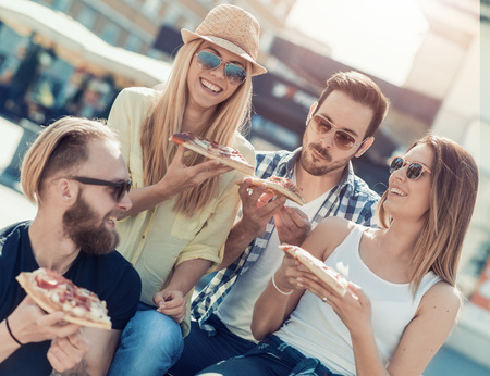 Close-up of four young cheerful people eating pizza,they are enjoying together.