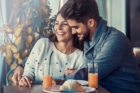 Bonne jeune couple ayant le petit déjeuner dans le café, en appréciant ensemble.
